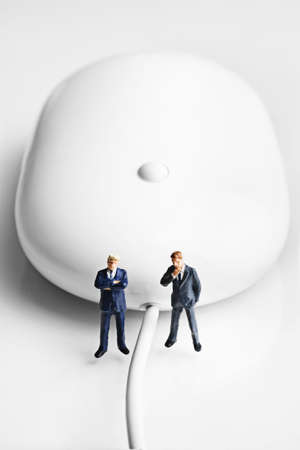 strategizing: Businessman figurines placed with a computer mouse
