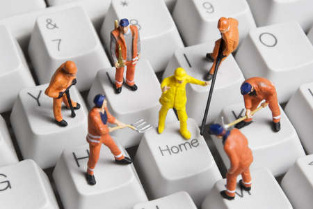 refurbish: Worker figurines posed around the Home key on a computer keyboard. Stock Photo