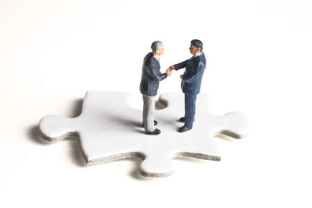 strategizing: Businessman figurines shaking hands while standing on a puzzle piece Stock Photo