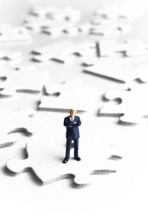 strategizing: Businessmen figurines standing on puzzle pieces  Stock Photo
