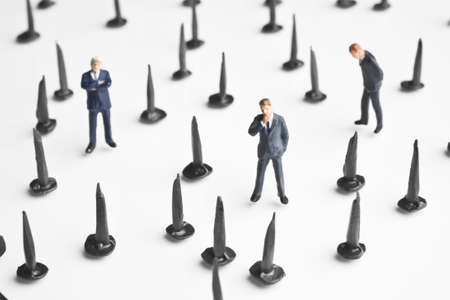 strategizing: Businessmen figurines placed with tacks