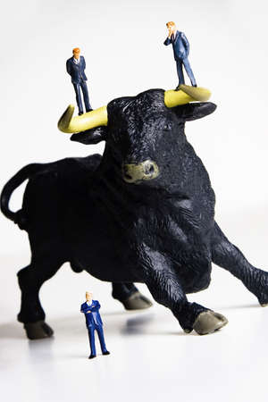 bearish market: Business figurines placed with a bull figurine.
