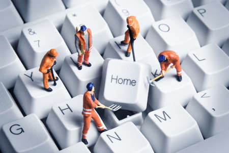 it technician: Worker figurines posed around the Home key on a computer keyboard. Stock Photo