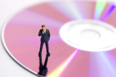 compact disk: Business figurine standing on a compact disk