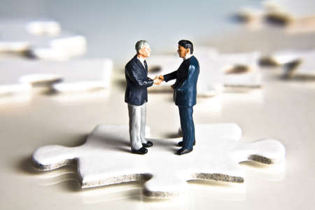 Businessman figurines shaking hands while standing on a puzzle piece Foto de archivo