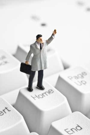 Businessman figurine placed on computer keyboard