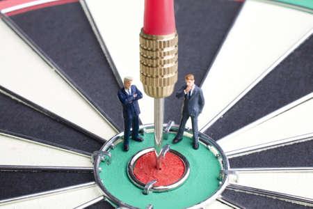 Zakenman beeldjes geplaatst op een dartsboard