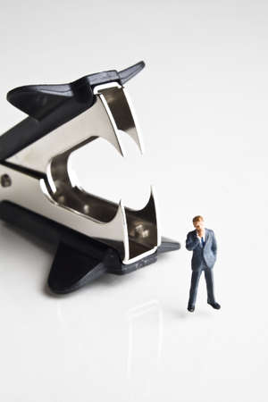 strategizing: Businessman figurines standing next to a staple remover Stock Photo