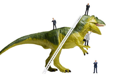 Business figurines and a small ladder placed on a dinosaur figurine. Stock Photo - 7165007