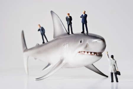 figurines: Business figurines placed with a shark figurine.