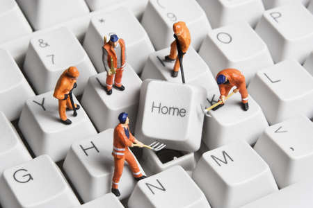 Worker figurines posed around the Home key on a computer keyboard. Foto de archivo