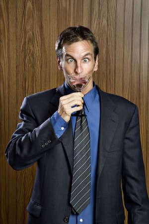drinking drunk: Businessman drinking a cocktail