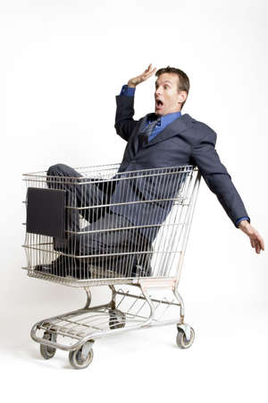 cart: Businessman sitting in a shopping cart looking scared