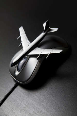 Toy airplane placed on a computer mouse photo