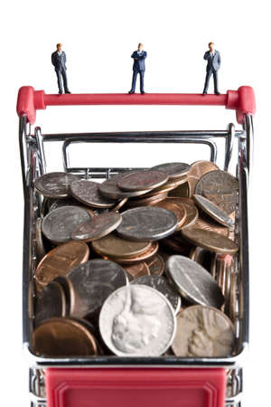 Businessman figurines standing on a shopping cart filled with coins Stock Photo - 7204752
