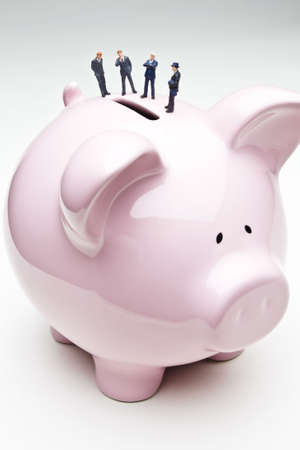 strategizing: Businessman figurines placed on a piggy bank Stock Photo