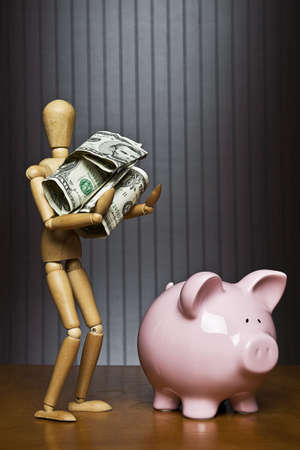 Manikin carrying a ball of money towards a piggy bank Stock Photo - 7204751