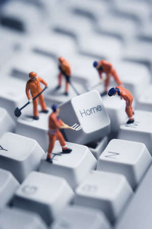 technical support: Worker figurines posed to look as though they are working on a computer keyboard.