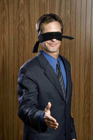 blindfolded: Businessman blindfolded offering hand for handshake