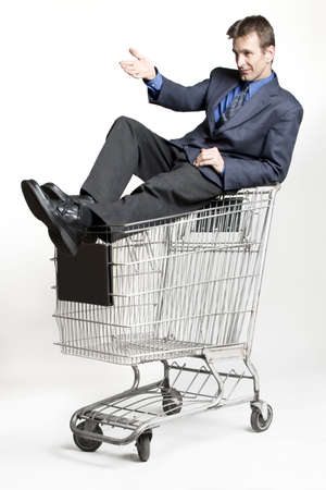 irony: Businessman sitting on a shopping cart