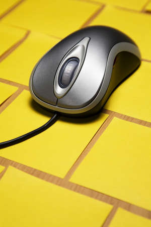 White computer mouse and long cord placed on a pattern of post it notes photo