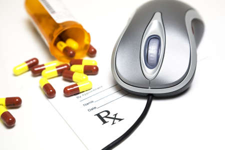 Computer mouse and pills placed on a prescription pad.