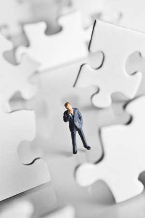 Figurine d'homme d'affaires entouré de pièces de puzzle Banque d'images - 7236880