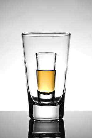 intoxicating: Shot glass half full with rum placed inside an empty beer glass Stock Photo