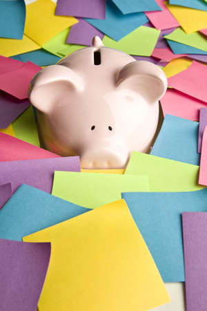 Piggy bank up to its nose in post it notes