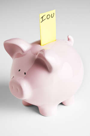 Piggy bank with IOU sticking out of its coin slot.