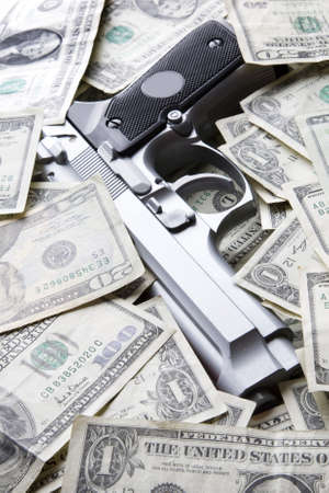 policing: Gun placed on a pile of dollar bills