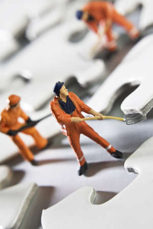 Worker figurines placed with puzzle pieces photo