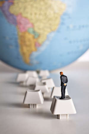Business figurine placed on computer keys that lead to an earth globe