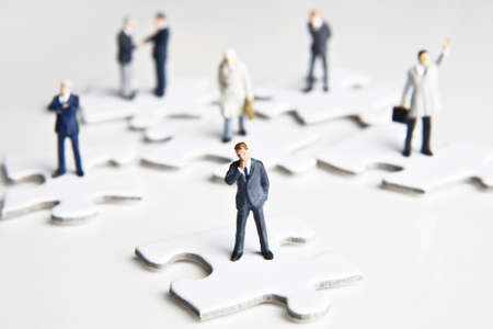strategizing: Businessman figurines placed with puzzle pieces