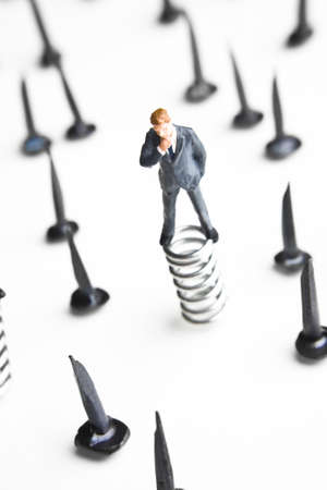 strategizing: Businessman figurines standing on springs surrounded by tacks   Stock Photo