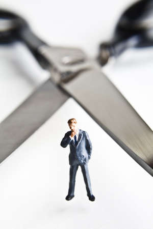 cutback: Businessman figurines standing next to scissors  Stock Photo