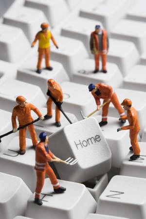 고치다: Worker figurines posed around the Home key on a computer keyboard. 스톡 사진