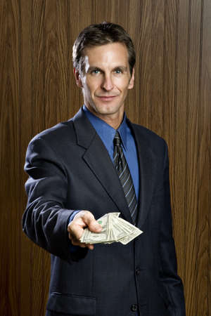 Businessman offering money smiling Stock Photo - 7342718
