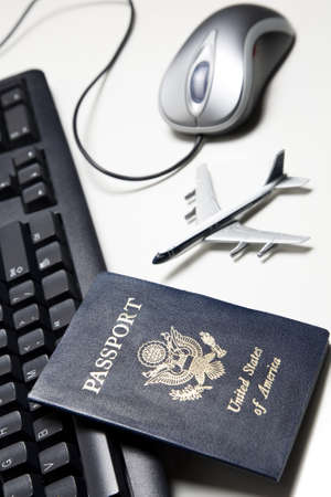 Computer mouse, toy airplane, passport and keyboard placed on a white tabletop.  Reklamní fotografie