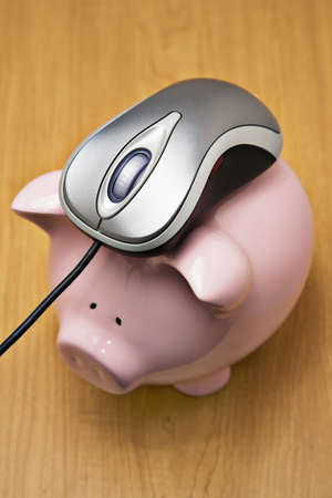 Metallic color computer mouse on top of a pink piggy bank photo