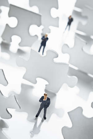 strategizing: Businessman figurine surrounded by puzzle pieces