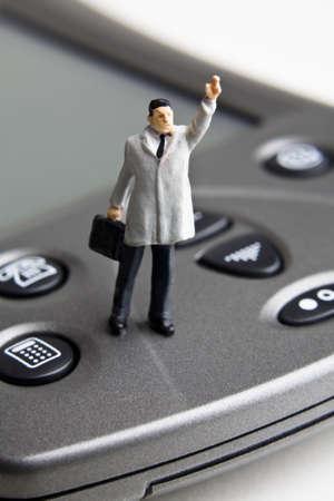 strategizing: Businessman figurine standing on a PDA