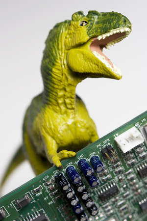 Dinosaur figurine with circuit board on white photo