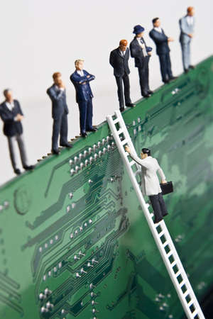 Business figurines and a small ladder placed against a circuit board Stock Photo - 7430683
