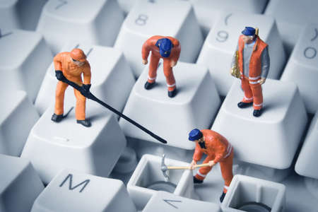 Worker figurines posed to look as though they are working on a computer keyboard. photo