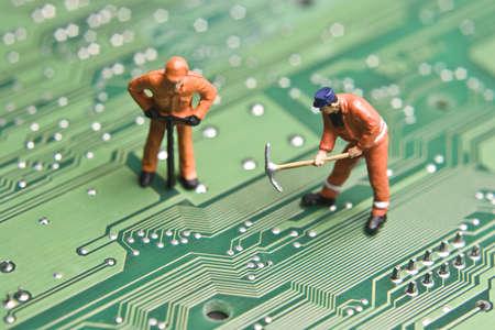 asamblea: Figurillas de trabajador que plantea a mirar como si est�n trabajando en una placa de circuito de equipo.