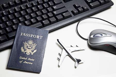 agencia de viajes: Avi�n de juguete, teclado, rat�n de ordenador y pasaporte colocan sobre una mesa blanca.