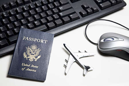 international internet: Computer mouse, toy airplane, passport and keyboard placed on a white tabletop.  Stock Photo