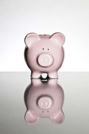 Piggy bank on a reflective tabletop