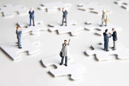 strategizing: Businessmen figurines standing on and around puzzle pieces